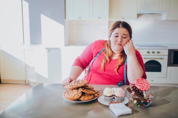 Fette junge frau in der küche, die süßes essen sitzt und isst. gelangweilte plus size modell blick auf pfannkuchen und süßigkeiten auf dem tisch.