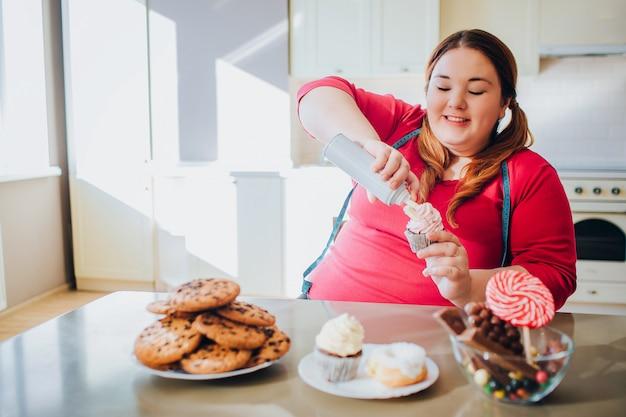 Fette junge frau in der küche, die süßes essen sitzt und isst. happy positive plus size modell etwas sahne auf pfannkuchen setzen. körper positiv. blaues maßband. süßigkeiten und kekse auf dem tisch.