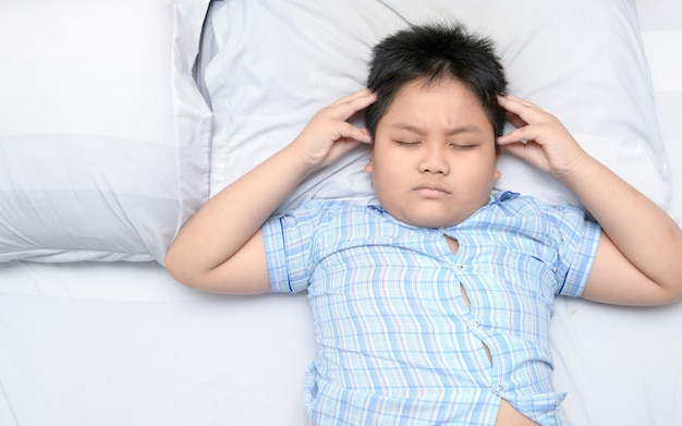 Fette jungenkopfschmerzen und lügen auf bett