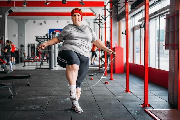 Fette verschwitzte frau, die übung mit seil im fitnessstudio tut. kalorien brennen, fettleibige weibliche person auf einem training im sportverein, fettleibigkeit