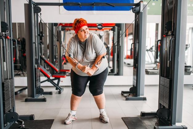 Fette verschwitzte frau, die übungsmaschine im fitnessstudio verwendet. kalorien brennende, fettleibige weibliche person im sportverein