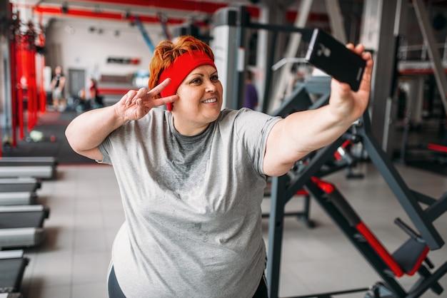 Fette verschwitzte frau macht selfie gegen trainingsgeräte im fitnessstudio. kalorien brennende, fettleibige weibliche person im sportverein