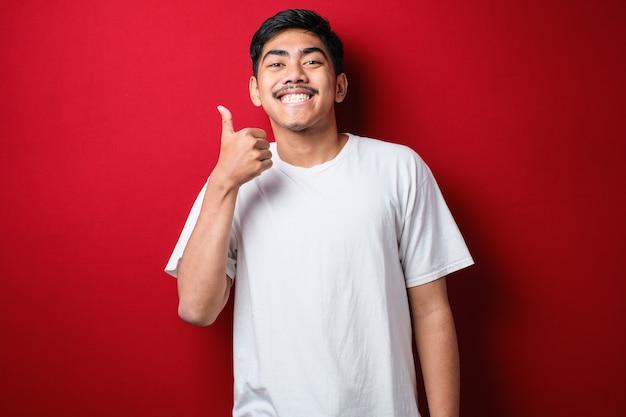 Fetter asiatischer kerl, der ein weißes t-shirt trägt, lächelt in die kamera und zeigt seine daumen nach oben. halbes körperporträt mit selektivem fokus vor rotem hintergrund.
