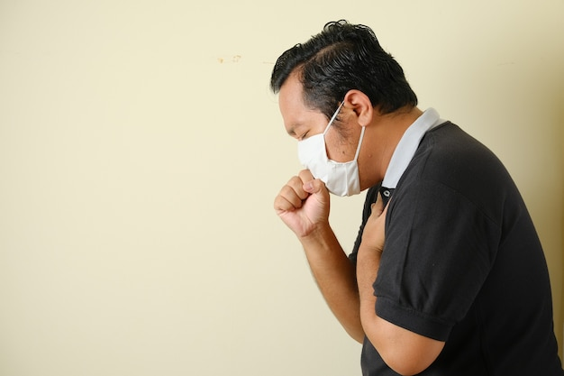 Fetter asiatischer kerl, der eine maske trägt, hustet, während er seinen mund mit den händen schließt, er fühlt sich unwohl. symptome einer corona-virus-erkrankung