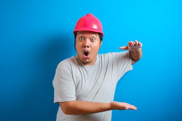 Fetter asiatischer mann, der einen helm trägt, präsentiert etwas in seiner hand, während er seitwärts schaut. der mann zeigte einen ausdruck von freude und überraschung