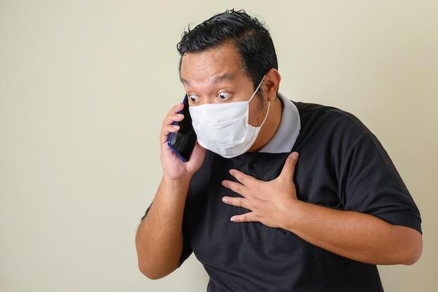 Fetter asiatischer mann mit maske sieht selbstbewusst aus, während er auf sein smartphone zugreift, der mann zeigt einen überraschten gesichtsausdruck