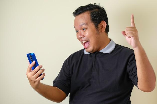 Fetter asiatischer mann sieht selbstbewusst aus, während er auf sein smartphone zugreift, der mann zeigt einen überraschten gesichtsausdruck