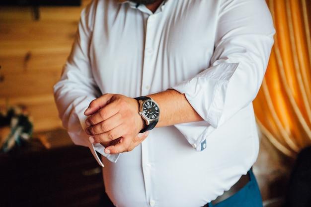 Fetter bräutigam umklammert stilvolles uhrenarmband an seinem handgelenk