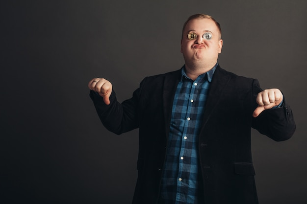 Fetter feiernder mann machen verrücktes gesicht. verrückter bitcoin-liebhaber mit goldener münze auf seinen augen