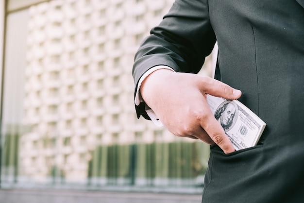 Fetter geschäftsmann, der geld in seine tasche einsetzt.