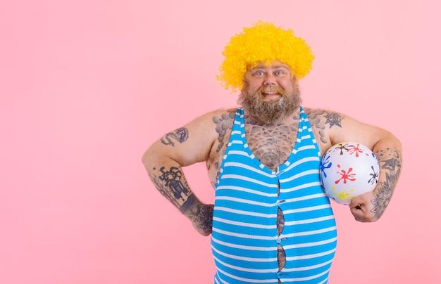 Fetter glücklicher mann mit bart und perücke spielt mit dem ball