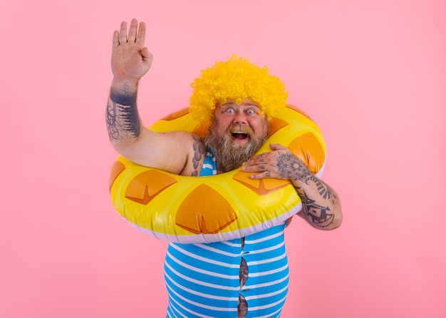 Fetter glücklicher mann mit perücke im kopf ist bereit, mit einem donut-lebensretter zu schwimmen