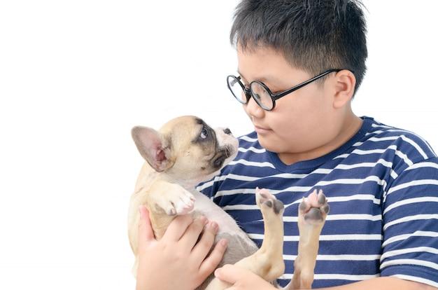 Fetter junge, der französische bulldogge lokalisiert hält