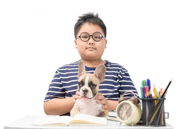 Fetter junge, der nette kleine französische bulldogge auf tabelle spielt