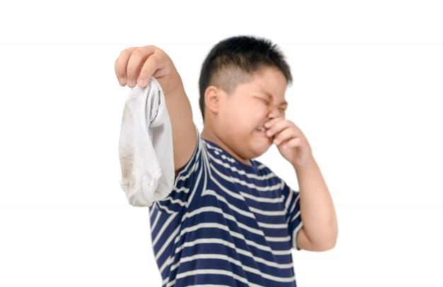 Fetter junge, der schmutzige stinky socken lokalisiert hält