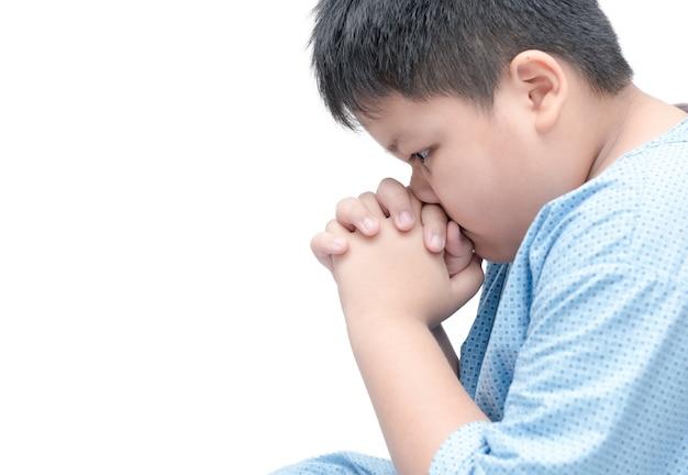 Fetter junge, der über weißem hintergrund lokalisiert wird. asiatische junge hand beten, hände gefaltet in gebet conce