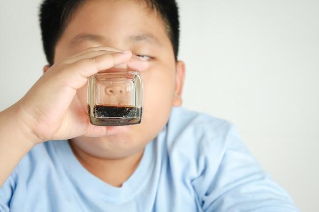 Fetter junge isst der körper sammelt zucker an. übergewicht ist nicht gut für die gesundheit.
