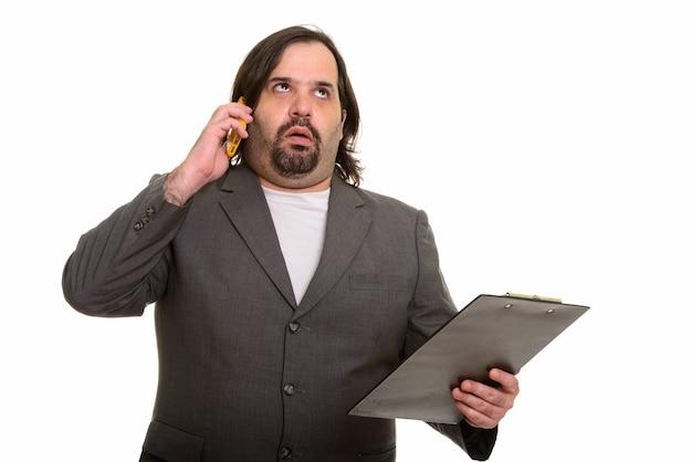 Fetter kaukasischer geschäftsmann, der genervt schaut, während er auf handy spricht und zwischenablage hält