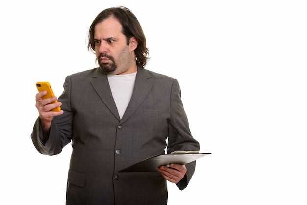 Fetter kaukasischer geschäftsmann, der gestresst schaut, während er handy und zwischenablage hält