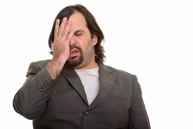 Fetter kaukasischer geschäftsmann, der müde lokalisiert auf weiß schaut