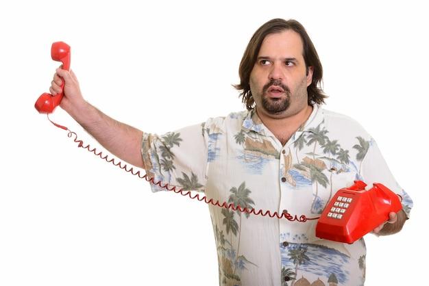 Fetter kaukasischer mann, der altes telefon hält, das auf weiß lokalisiert genervt aussieht