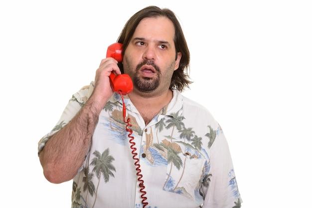 Fetter kaukasischer mann, der am alten telefon spricht, das müde lokalisiert auf weiß aussieht