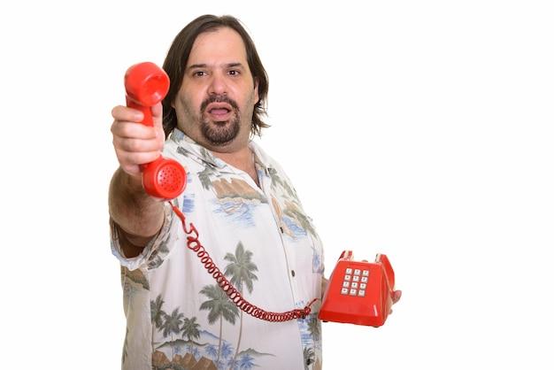 Fetter kaukasischer mann, der anruf vom alten telefon weiterleitet, das auf weiß isoliert wird