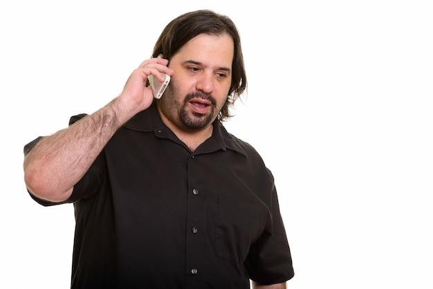 Fetter kaukasischer mann, der auf handy lokalisiert auf weiß spricht