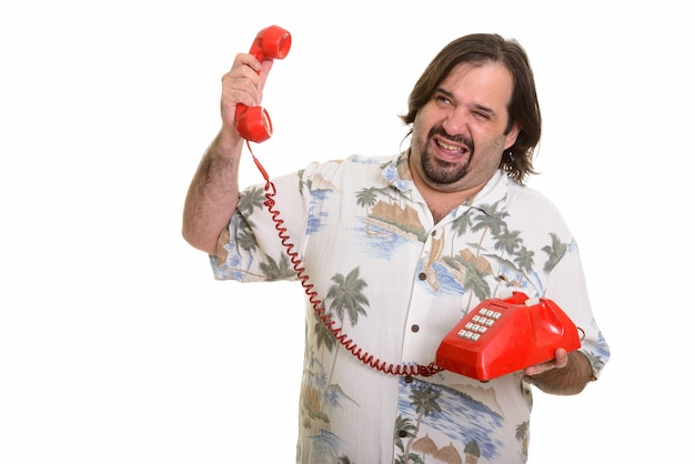 Fetter kaukasischer mann, der gestresst schaut, während er lautes altes telefon hält
