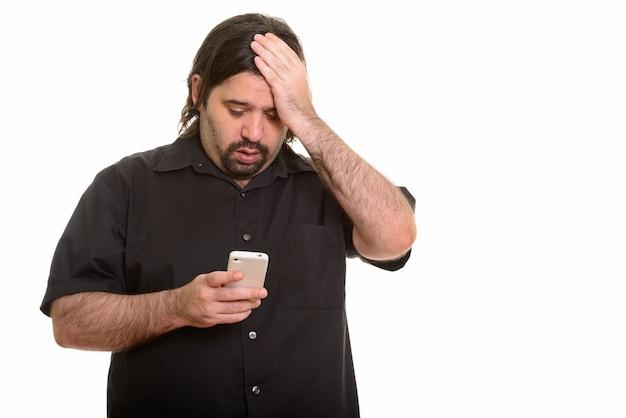 Fetter kaukasischer mann, der müde schaut, während handy lokalisiert auf weiß verwendet