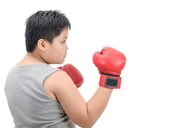 Fettes jungenkind, das mit roten boxhandschuhen kämpft