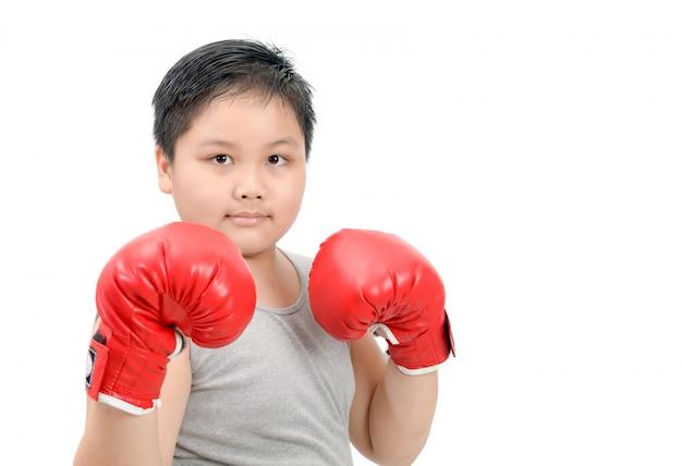 Fettes kind, das mit den roten boxhandschuhen lokalisiert kämpft