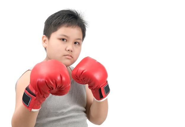 Fettleibiges fettes jungenkind, das mit roten boxhandschuhen kämpft