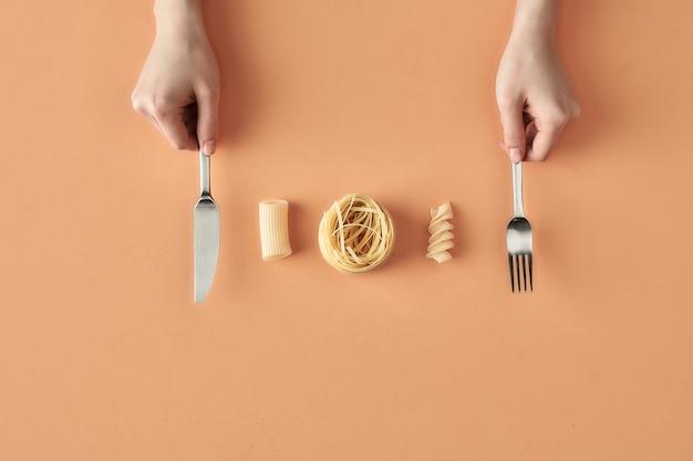Fettuccine, tortiglioni, fusilli pasta und hände mit gabel und messer