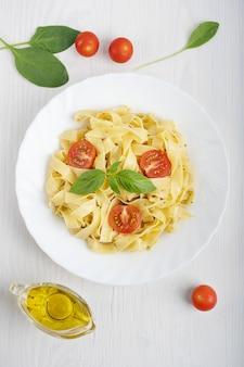 Fettucine nudeln verziert mit geschnittenen tomaten und basilikumblättern auf weißem holztisch