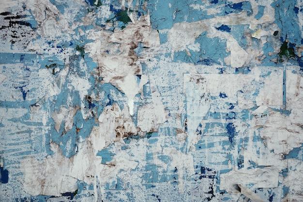Fetzen alter zerrissener papierplakate an der wand. grunge städtischen hintergrund