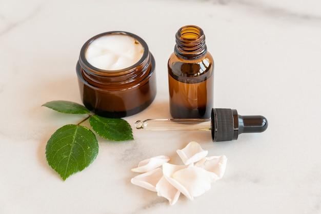 Feuchtigkeitscreme-cremeglas, serum in glasflasche auf weißem hintergrund mit rosenblättern. set für schönheitsprodukte zur haut- und körperpflege. markenloses paket.