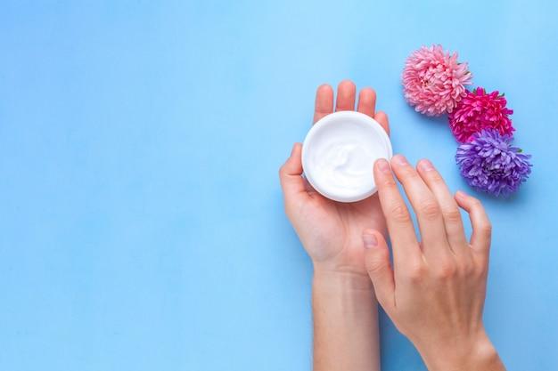 Feuchtigkeitsspendende handcreme und blumen. handpflege. beseitigung von trockener haut der hände.