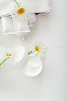 Feuchtigkeitsspendende hautcreme im weißen glas mit kamillenblüten. mockup weißes plastikglas für feuchtigkeitscreme, lotion auf weißem hintergrund. stellen sie weiße hautpflegeprodukte in tuben und flaschen ein. ansicht von oben.