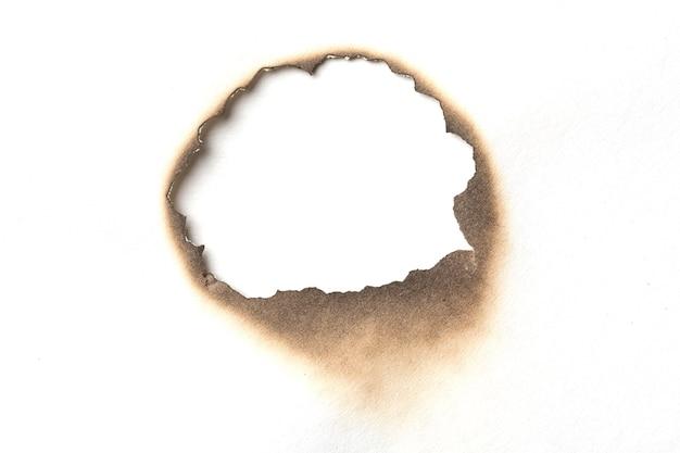 Feuer brannte loch weißbuch hintergrundtextur. papierbrandfleckfleck.