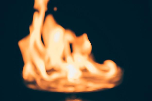 Feuer, das auf unscharfem schwarzem hintergrund brennt