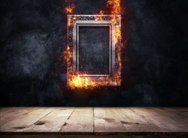 Feuer, das silbernen antiken bilderrahmen auf dunkler schmutzwand mit der holztischoberseite brennt, leeren bereites zur produktanzeige oder zur montage.