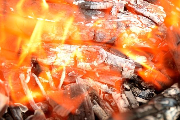 Feuer; gelbe flammen eines hölzernen feuers gegen schwarzen hintergrund
