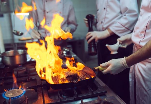 Feuer in der küche. feuergas brennt auf eisenpfanne, feuer sehr heiß rühren