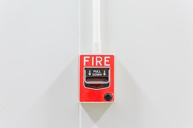 Feueralarmschalter auf weißer fabrikwand für warn- und sicherheitssystem