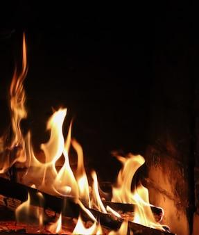 Feuerflammen auf schwarzem hintergrund das geheimnis des feuerraums für textkopien ihrer worte vertikal