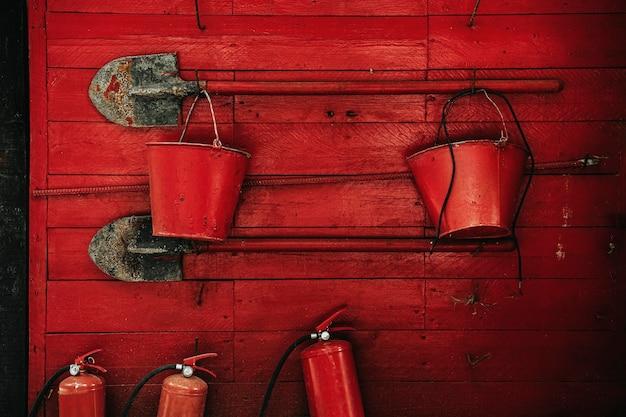 Feuerlöschwerkzeuge. schaufeln, eimer, feuerlöscher an einer roten holzwand