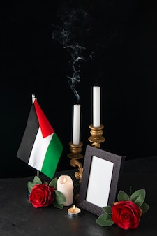 Feuerlose kerzen mit palästinensischer flagge und blumen auf dunkler oberfläche