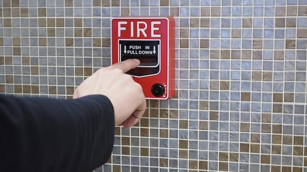 Feuermelder oder alarm- oder klingelwarngeräte und rechte hand. im gebäude für notfall und sicherheit.