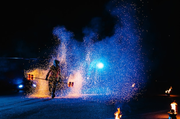 Feuershow, flammentanz, männlicher meister, der mit feuerwerk jongliert, performance im freien, zeichnet eine feurige figur im dunkeln, helle funken in der nacht. ein mann im anzug led tanzt mit feuer.